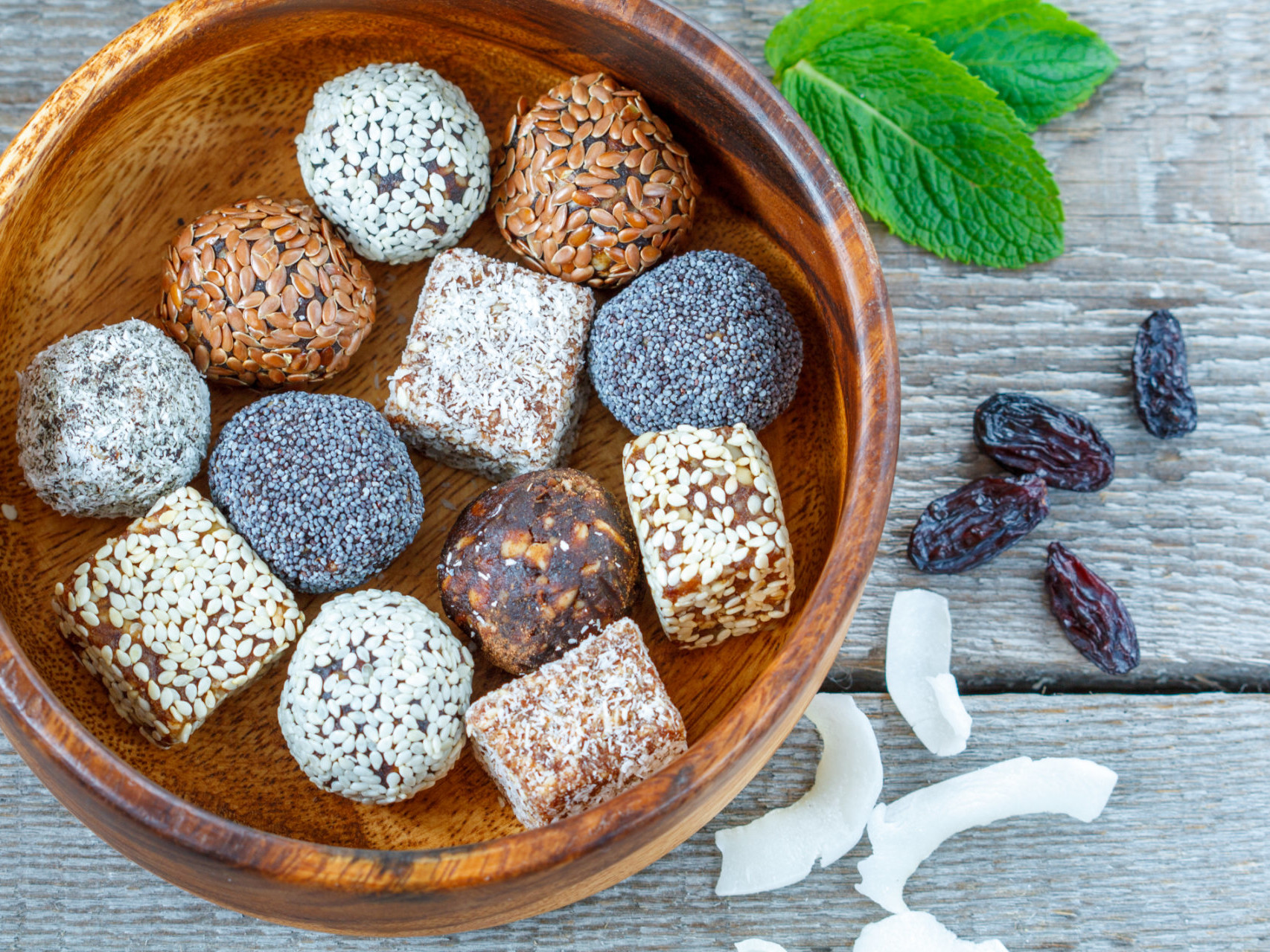 Healthy raw energy balls with cocoa, coconut, sesame, chia in a wooden bowl.
